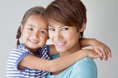 Familia feliz con la sonrisa, hija positiva y la madre Imágenes de archivo libres de regalías