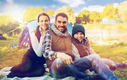 Familia feliz con la tienda en el camping Imagen de archivo libre de regalías