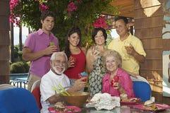 Familia feliz con las bebidas en el pórtico Fotos de archivo libres de regalías