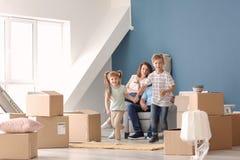 Familia feliz con las cajas y las pertenencia de cartón dentro El trasladarse a nueva casa imágenes de archivo libres de regalías