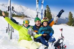 Familia feliz con las manos para arriba en nieve después de esquiar Foto de archivo libre de regalías