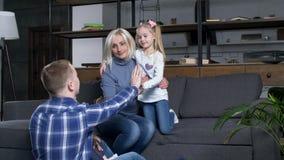 Familia feliz con las muchachas del preescolar que tocan las manos almacen de video
