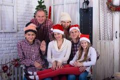 Familia feliz con los amigos, en los sombreros de Papá Noel Fotos de archivo libres de regalías