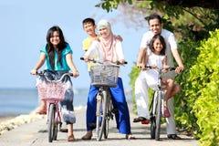 Familia feliz con los cabritos que montan las bicis Imágenes de archivo libres de regalías