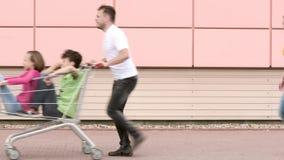 Familia feliz con los carros de la compra almacen de metraje de vídeo