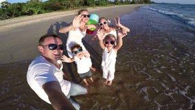 Familia feliz con los globos que juegan en la playa en el tiempo del día metrajes