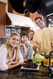 Familia feliz con los niños adolescentes en cocina Imagen de archivo libre de regalías