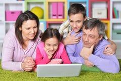 Familia feliz con los niños detrás del ordenador portátil Foto de archivo libre de regalías