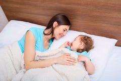 Familia feliz con los niños en cama Madre e hija i sonriente Fotografía de archivo