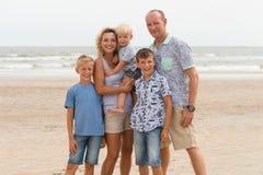 Familia feliz con los niños en la playa soleada Imagen de archivo libre de regalías