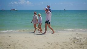 Familia feliz con los niños que caminan en la playa arenosa Isla tropical, en un día caliente almacen de metraje de vídeo
