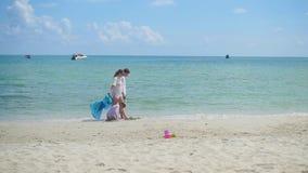 Familia feliz con los niños que caminan en la playa arenosa Isla tropical, en un día caliente almacen de video