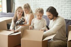 Familia feliz con los niños que desempaquetan las cajas que se mueven en nuevo hogar foto de archivo libre de regalías