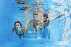 Familia feliz con los niños que nadan con la diversión en piscina Imagenes de archivo