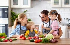 Familia feliz con los niños que preparan la ensalada vegetal imagenes de archivo
