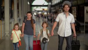 Familia feliz con los niños que van en el ferrocarril, los padres y los niños viajando y caminando en el aeropuerto almacen de metraje de vídeo