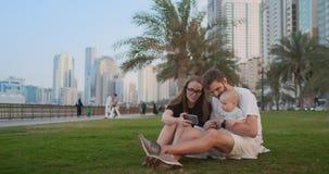 Familia feliz con los niños uno que se sientan junto en hierba en parque y que toman un selfie Con smartphone almacen de video