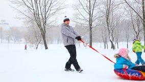 Familia feliz con los niños y un perro que se divierte en un parque nevado en invierno almacen de metraje de vídeo