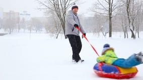 Familia feliz con los niños y un perro que se divierte en un parque nevado en invierno almacen de video