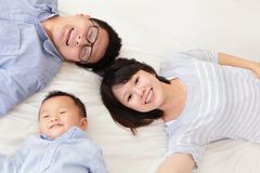Familia feliz con los niños en cama Foto de archivo libre de regalías