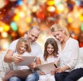 Familia feliz con los ordenadores de la PC de la tableta Foto de archivo