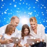 Familia feliz con los ordenadores de la PC de la tableta Foto de archivo libre de regalías
