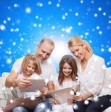 Familia feliz con los ordenadores de la PC de la tableta Imagen de archivo libre de regalías