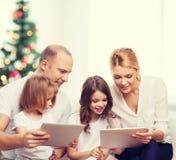 Familia feliz con los ordenadores de la PC de la tableta Fotografía de archivo