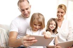 Familia feliz con los ordenadores de la PC de la tableta en casa Foto de archivo libre de regalías
