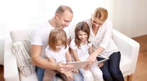 Familia feliz con los ordenadores de la PC de la tableta en casa Imagen de archivo libre de regalías