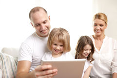 Familia feliz con los ordenadores de la PC de la tableta en casa imagen de archivo