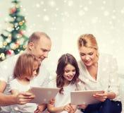 Familia feliz con los ordenadores de la PC de la tableta en casa imágenes de archivo libres de regalías