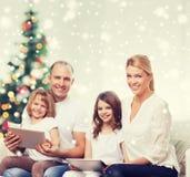 Familia feliz con los ordenadores de la PC de la tableta en casa Fotos de archivo libres de regalías