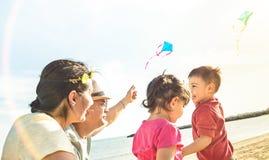 Familia feliz con los padres y los niños que juegan así como cometa Fotos de archivo