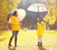 Familia feliz con los paraguas en día lluvioso del otoño soleado Imagenes de archivo
