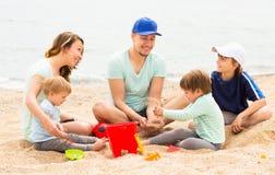 Familia feliz con los pequeños niños en la playa arenosa Imagen de archivo