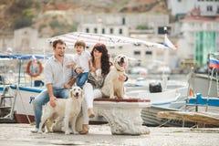 Familia feliz con los perros en el Quay en el verano Foto de archivo