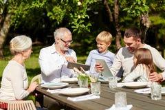 Familia feliz con PC de la tableta en la tabla en jardín Imagenes de archivo