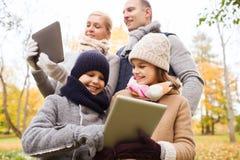 Familia feliz con PC de la tableta en parque del otoño Foto de archivo