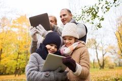 Familia feliz con PC de la tableta en parque del otoño Imágenes de archivo libres de regalías