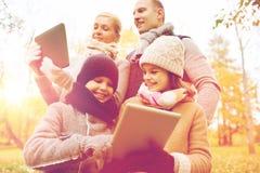 Familia feliz con PC de la tableta en parque del otoño Imagen de archivo