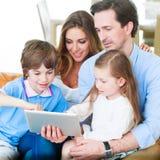 Familia feliz con PC de la tableta imagen de archivo libre de regalías