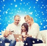 Familia feliz con PC de la tableta y la tarjeta de crédito Fotografía de archivo libre de regalías