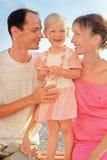 Familia feliz con poco en la playa Foto de archivo