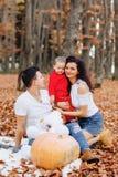 Familia feliz con poco niño lindo en parque en la hoja amarilla con imagenes de archivo