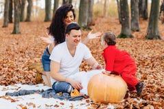 Familia feliz con poco niño lindo en parque en la hoja amarilla con foto de archivo