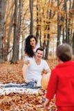 Familia feliz con poco niño lindo en parque en la hoja amarilla con fotografía de archivo