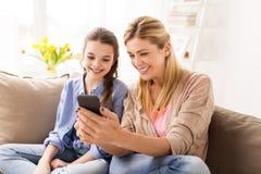 Familia feliz con smartphone en casa Imagenes de archivo