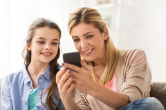 Familia feliz con smartphone en casa Foto de archivo