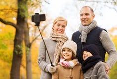 Familia feliz con smartphone y monopod en parque Foto de archivo libre de regalías